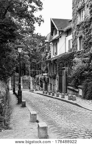 The charming old street of the Montmartre hill are full of art galleries cafes and shops to walk about. Summer day in black and white. Paris France