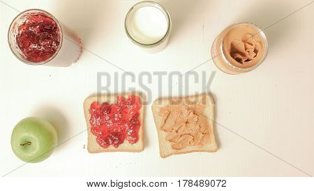 Breakfast with a sandwich with jam, peanut butter, a glass of milk and an apple. Jar with jam and peanut butter on the table