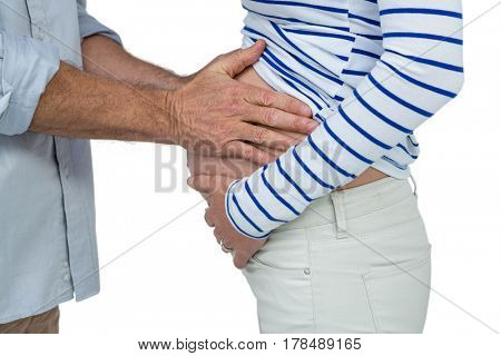 Man touching pregnant womans belly on white background