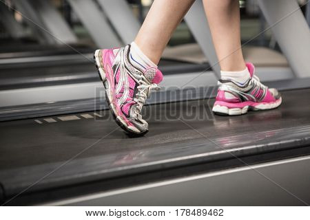 Lower section of a woman on a treadmill at the gym