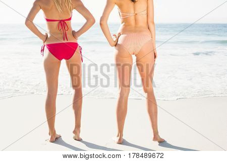 Mid-section of women standing in bikini on the beach on a sunny day