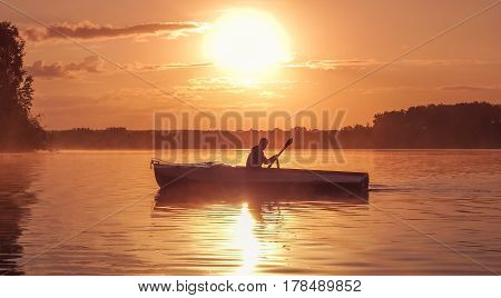 A young guy rides a boat on a lake during a golden sunset. Image of silhouette sunset. Man rowing a boat in backlight of the sun. Contre-jour backlight back lit fill light bright spot. Unity with nature concept