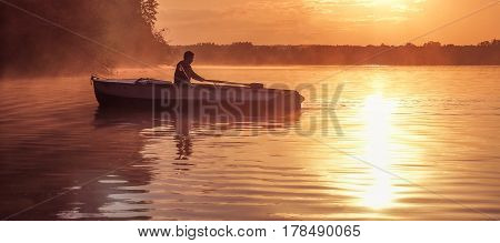 A young guy rides a boat on a lake during a golden sunset. Image of silhouette sunset. Man rowing a boat in backlight of the sun. Contre-jour backlight back lit fill light bright spot
