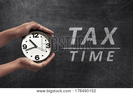 People Hand Holding Black Alarm Clock Beside Tax Time Announcement