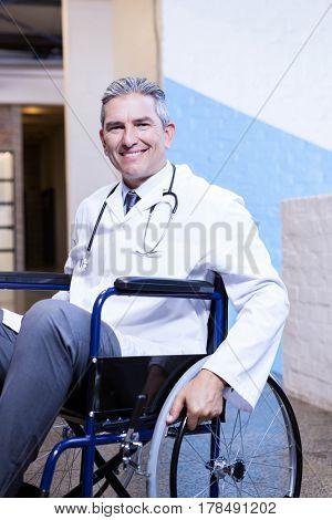 Portrait of happy male doctor sitting on wheel chair in hospital
