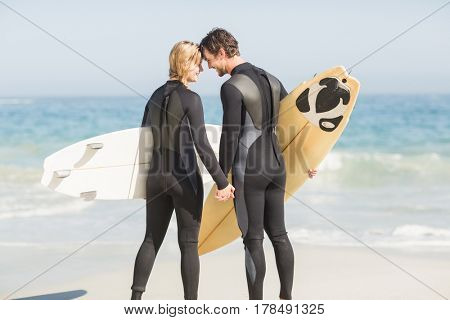 Happy couple standing head to head with surfboard on the beach