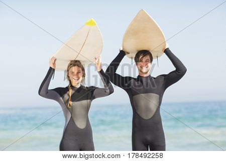 Portrait of couple in wetsuit carrying surfboard over head on a sunny day