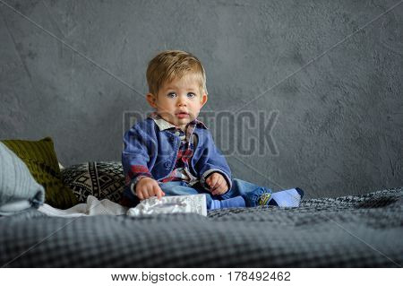 Portrait of little boy. Cute kid looks in camera serious look. Child is dressed in small men's jacket. He has an adult hairstyle. It looks funny and touches. Lop-eared round big eyes chubby cheeks.