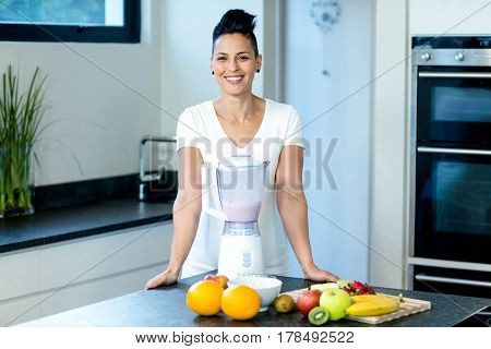 Pregnant woman smiling while standing in kitchen with blender and fruits on worktop