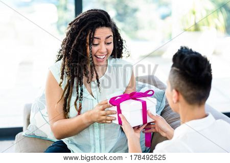Woman receiving a gift from her partner in living room
