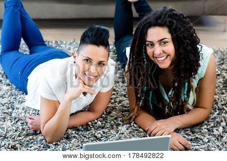 Portrait of smiling lesbian couple lying on rug and using laptop in living room