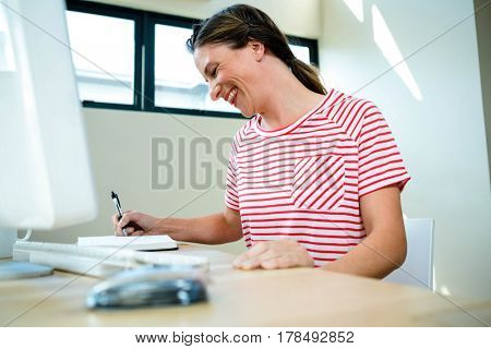 smiling business woman writing in her notepad on her desk