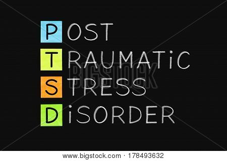 PTSD acronym Post Traumatic Stress Disorder handwritten with white chalk on blackboard.