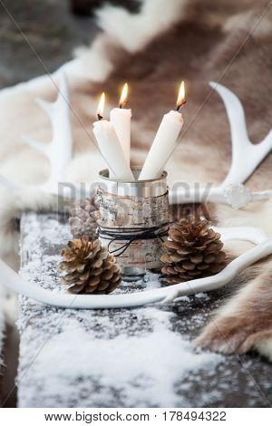 Three white candles in tin can