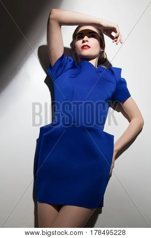 Pretty young woman wearing blue dress closing face from the light. Vertical studio shot.