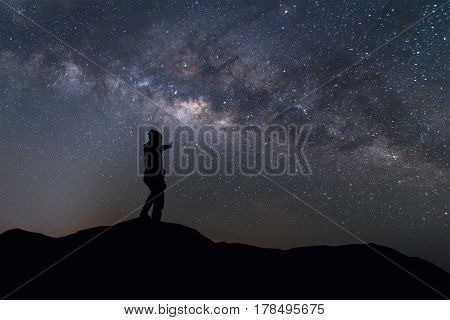 Milky Way landscape. Silhouette man thump up and standing on top of mountain with night sky and bright star on background.