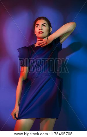 Stylish pretty female looking away with the hand near her neck. Vertical studio shot.