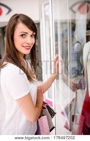 Portrait of beautiful woman window shopping in mall