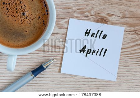 Hello April - notice on wooden table with morning coffee mug. Spring time concept.