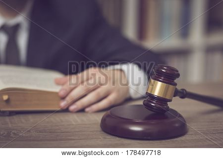 Detail of a judge sitting at his desk studying new laws and legislation. Selective focus