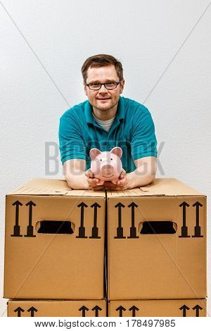 Happy Man Holds His Piggy Bank High, In His New Apartment.