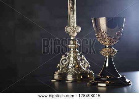 Catholic religion theme.  The cross and gold chalice on glass table and stone background.