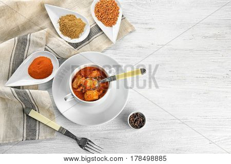 Soup pot with chicken tikka masala on wooden table
