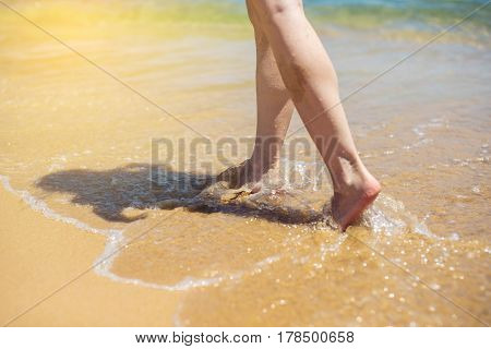 Woman Walks Barefoot In The Sand Washed By Sea Wave