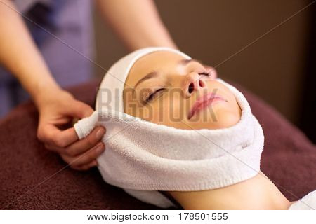 people, beauty, lifestyle and relaxation concept - beautiful young woman lying with closed eyes and having face massage with towel at spa