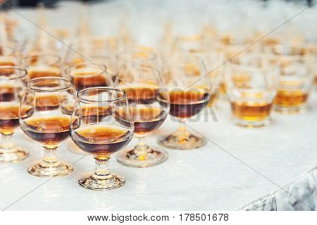 Row of glasses with whiskey or cognac on the table. Strong alcohol in a bar or restaurant. Transparent glasses with an alcoholic drink