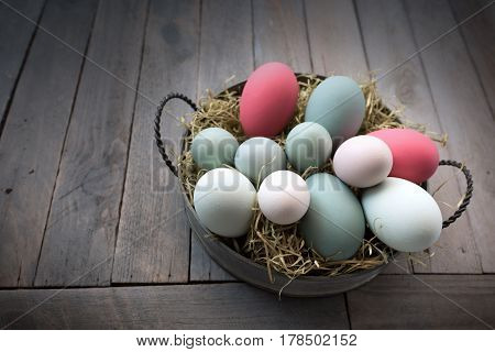 Easter basket with colorful eggs in country house style close up