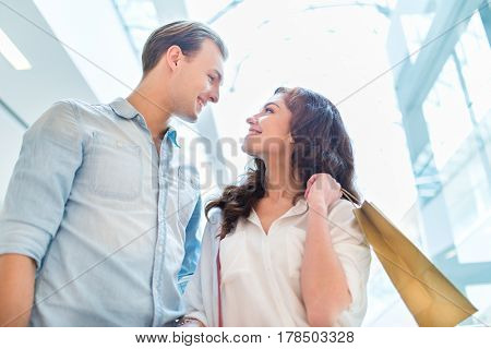 Happy smiling couple doing shopping together in a shopping mall