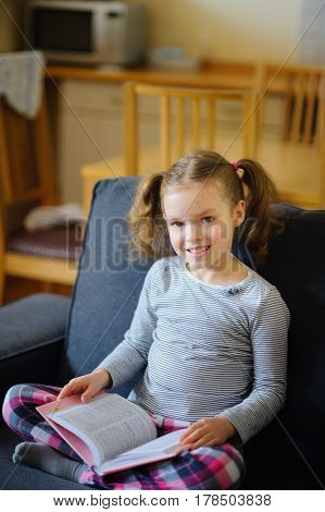 Cute girl of younger school age reads the book. She sits having crossed legs on a soft sofa. The open book lies at the child on a lap. Girl has distracted from reading and looks with a smile in the camera.