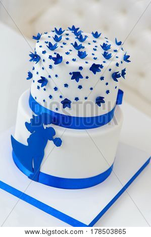 White wedding cake with blue flowers and a bow. Also with the figures of the bride and groom.
