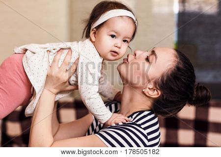 Young happy woman holding baby girl in hands. Raises her daughter in the air and kissing.