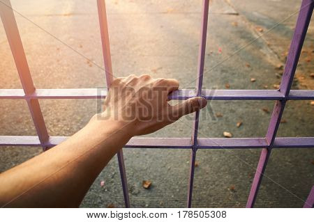 Close up Man hands are holding the cage door