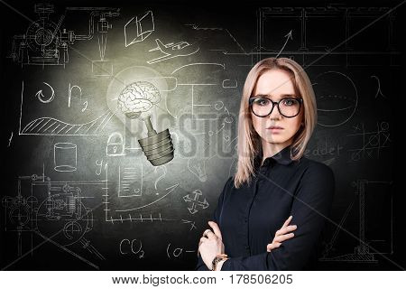 Thoughtful woman near bright bulb over icons on chalk board