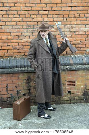 Vertical portrait image of a mature man dressed as a 1940s gangster, holding a shot gun.
