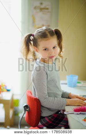 The little schoolgirl performs homework. The girl sits at a desk half-turned to the camera and smiles. On a table school supplies and different personal objects. To the child it is comfortable.