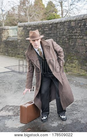 Vertical portrait image of a mature man dressed as a 1940s gangster, holding a suitcase