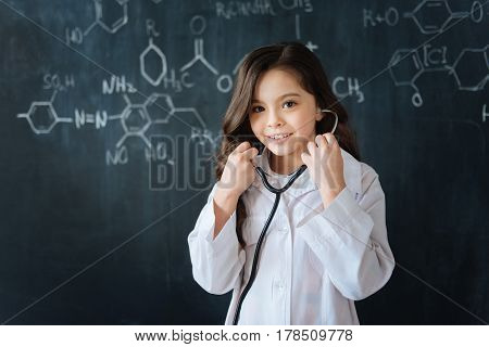 Testing professional equipment. Shy charming gifted girl standing near the blackboard in the laboratory while enjoying medicine lesson and using the stethoscope
