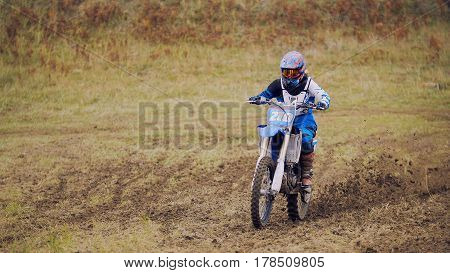 Motocross racer on dirt bike at sport track - fast and danger, telephoto