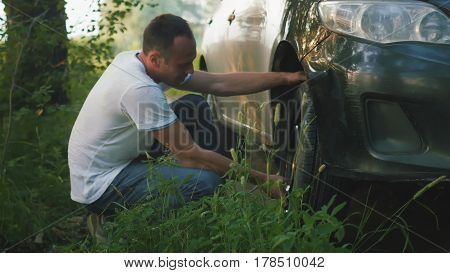 Man changes broken wheel of a car in the woods, telephoto