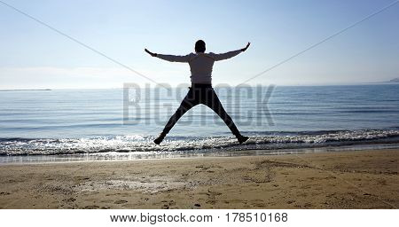 Boy jumping in the shore of a beach