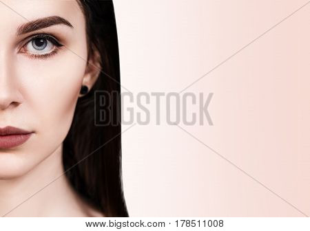 Half-face portrait of beautiful sensual woman over beige background.