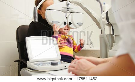 High technology in ophthalmology - optometrist in clinic checking little girl's vision - children's medicine, horizontal