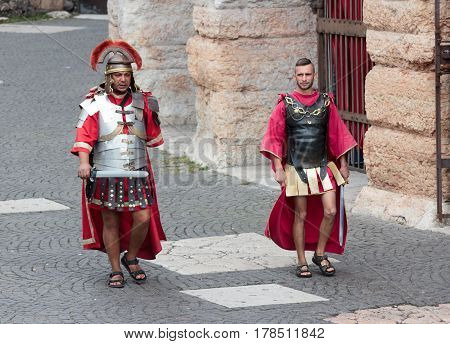 Verona Italy September 27 2015 : Two men dressed in the form of Roman legionaries walk around the Piazza Bra square near the Arena in Verona Italy