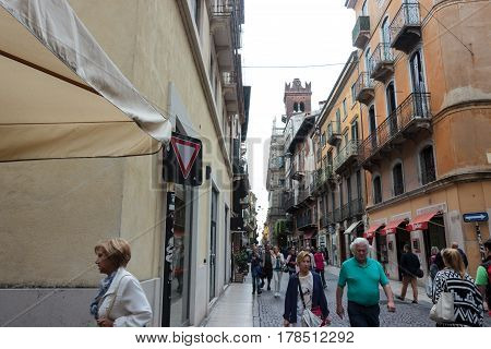 Tourists Walk Along Via Rosa, Inspect And Photograph In Verona