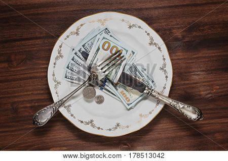 New US dollars notes and some coins - quarters and dimes - on the plate with silver utensils