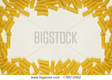 Pasta tortiglioni on the textured oldened paper background like a frame